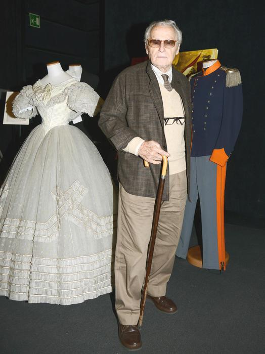 Il costumista Piero Tosi, posa vicino agli abiti di scena di Claudia Cardinale e di Alain Delon, durante la conferenza stampa per la presentazione della versione restaurata del film di Luchino Visconti 'Il Gattopardo', nella Casa del Cinema di Villa Borghese a Roma, 25 ottobre 2013. ANSA/CLAUDIO ONORATI